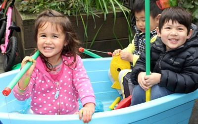 happy children sitting in boat at childcare